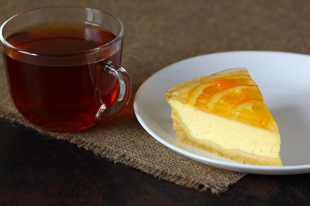 白い皿にオレンジとチーズケーキ、黄麻布のテーブルクロスにお茶とガラスのマグカップ。 Premium写真