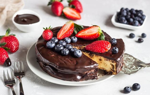 Cheesecake with raisin decorated with chocolate glaze, strawberries and blueberries. Premium Photo