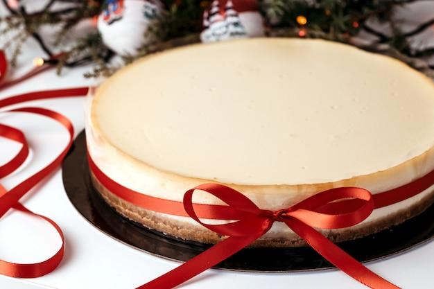 Cheesecake with red ribbon. Premium Photo