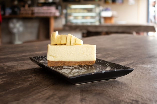 Cheesecake with topped durian fruit and durian cream on wooden desk background. summer fruit for dessert in thailand and asia Premium Photo