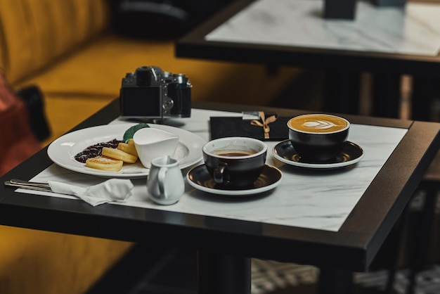 Cheesecakes for breakfast with jam, cappuccino and espresso, and camera. banner for cafes and restaurants Premium Photo