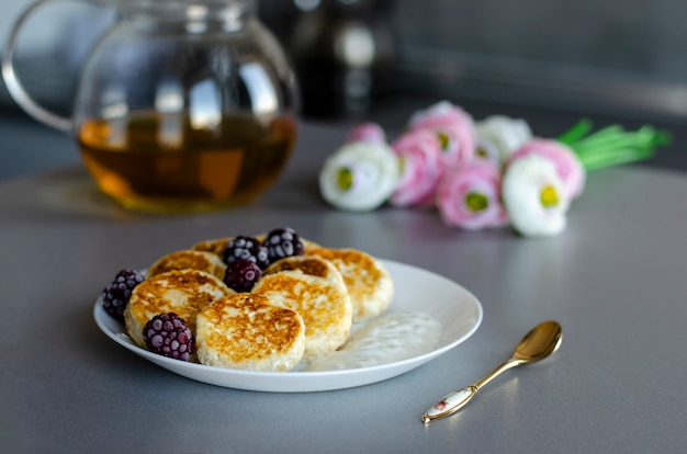 Cheesecakes from cottage cheese with blackberries on gray table with transparent tea pot, tea spoon and flowers Premium Photo