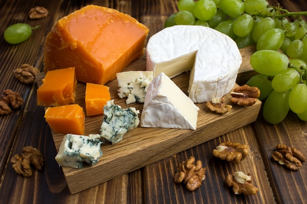 Сыры, виноград и орехи на коричневом деревянном Premium Фотографии
