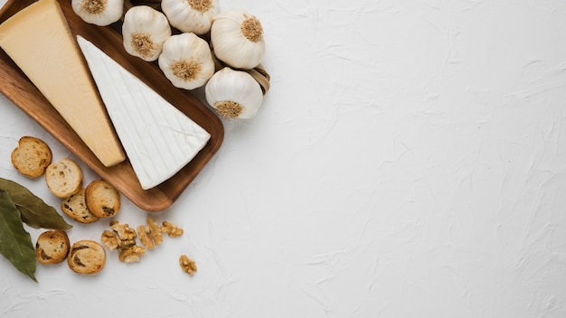 Cheeses piece on wooden tray with bay leaves; bread slice; walnut and garlic bulb on white surface Free Photo