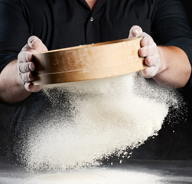 Повар мужчина в черной форме держит в руках круглое деревянное сито и просеивает белую пшеничную муку на черном пространстве, частицы разлетаются в разные стороны, пыльное пространство Premium Фотографии