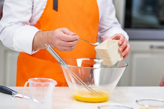 Chef adds sugar to the beaten eggs Premium Photo