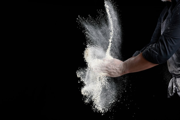 Chef in black uniform sprinkles white wheat flour in different directions, product scatters dust, black background, copy space Premium Photo