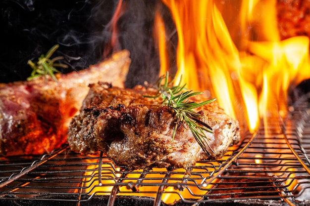 Chef cook fries meat, beef steak on an open fire in a restaurant Premium Photo
