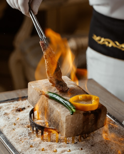 Chef cooking beef steak piece with clip on stone brick on fire Free Photo