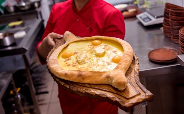 シェフがチーズと卵でハチャプリを調理します。グルジアの郷土料理。飲食店。 Premium写真