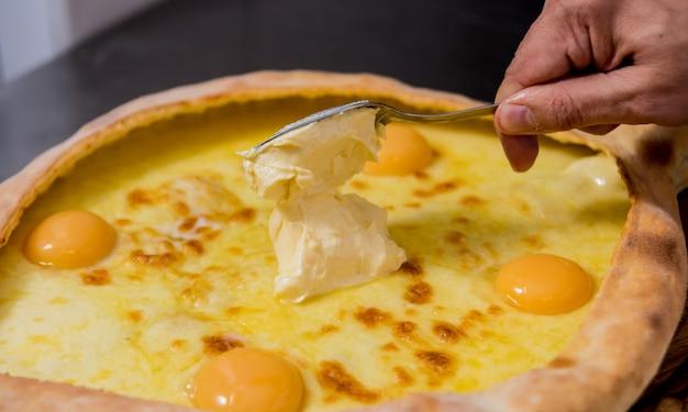 シェフがチーズと卵でハチャプリを調理します。グルジアの郷土料理。 Premium写真