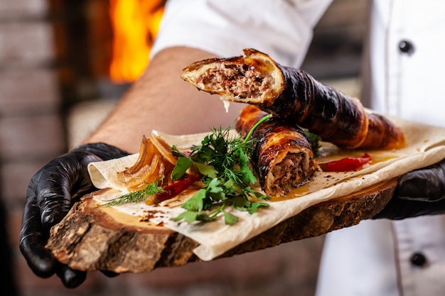 Chef cooking meat lyulya kebab in the dough on the grill. Premium Photo