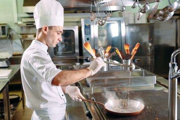 中華鍋で野菜を調理するシェフ。浅い被写界深度。 Premium写真