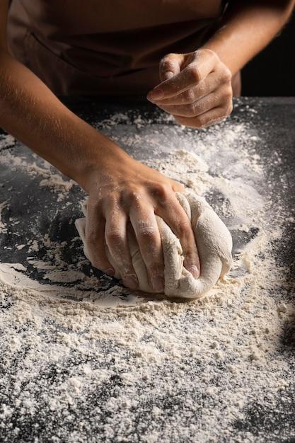 Chef ricopre l'impasto nella farina per renderlo meno appiccicoso Foto Gratuite
