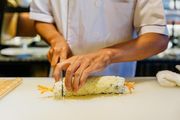 Шеф-повар приготовил суши маки с рисом, креветками, темпурой, авокадо и сыром. Premium Фотографии