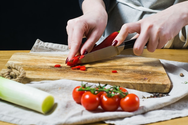 The chef cuts chili peppers on a wooden chopping board. Premium Photo