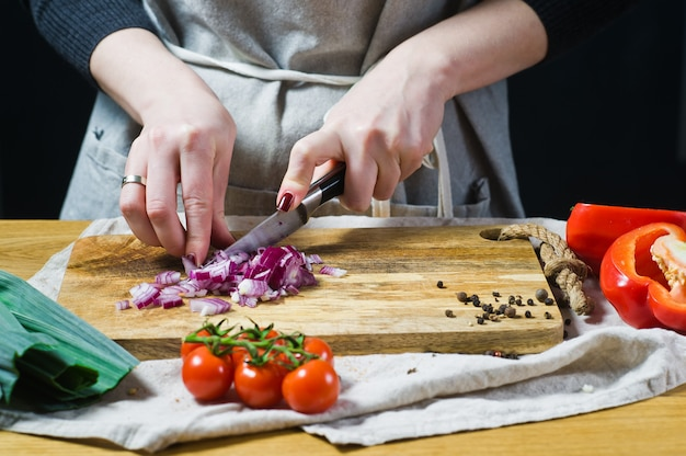The chef cuts red onions on a wooden chopping board. Premium Photo