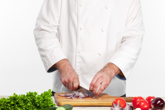 Шеф-повар нарезает лук на своей кухне Бесплатные Фотографии