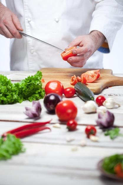 Шеф-повар режет красный помидор на своей кухне Бесплатные Фотографии