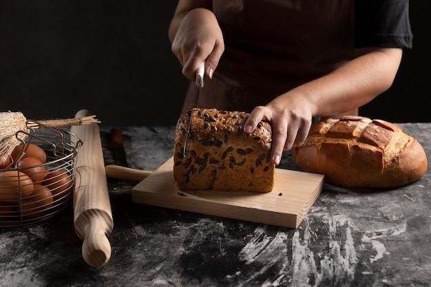 まな板の上で焼きたてのパンを切るシェフ 無料写真