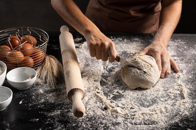 テーブルの上でパン生地を切るシェフ 無料写真