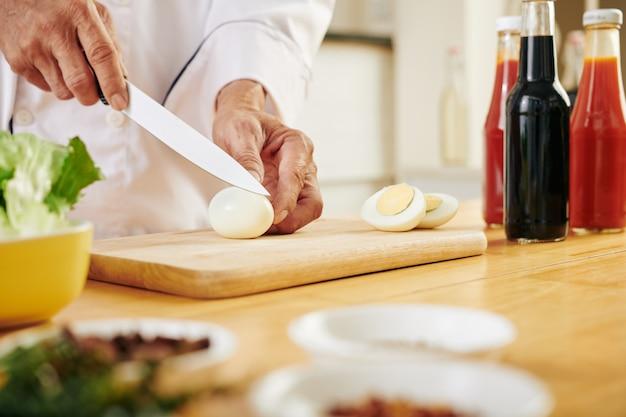 シェフが鶏の卵を切る Premium写真