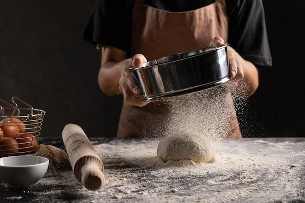 Шеф-повар посыпает тесто мукой Бесплатные Фотографии