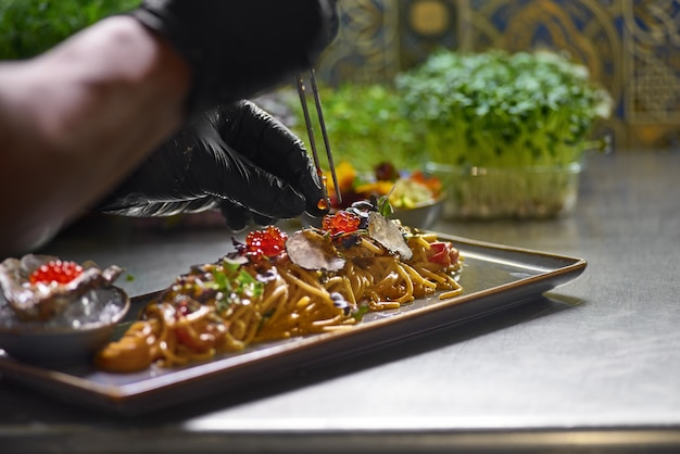 The chef garnishes with red caviar a seafood spaghetti dish, selective focus. Premium Photo