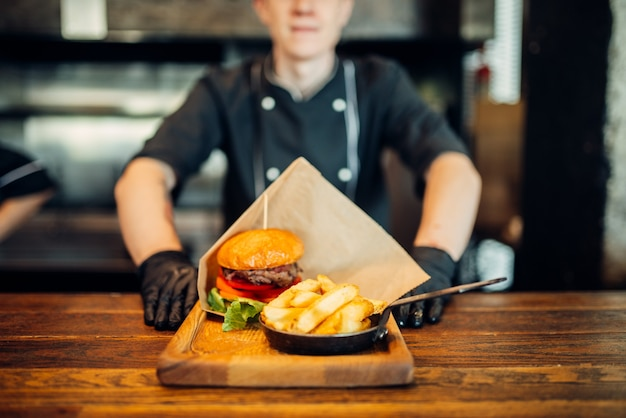 Chef in gloves against juicy burger with fresh steak. a real hamburger cooking, food preparation on kitchen, grilled meat Premium Photo