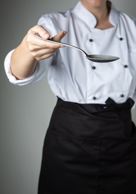 Chef hand spoon cooking prepare  food  in kitchen restaurant want you to taste delicious Premium Photo