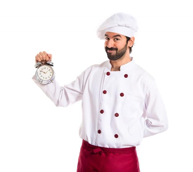 Chef in possesso di un orologio su sfondo bianco Foto Gratuite