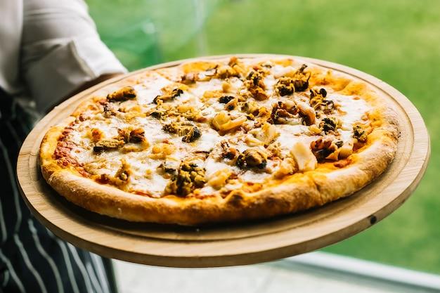 エビ、ムール貝、イカ、イカ、チーズのシーフードピザを保持しているシェフ 無料写真