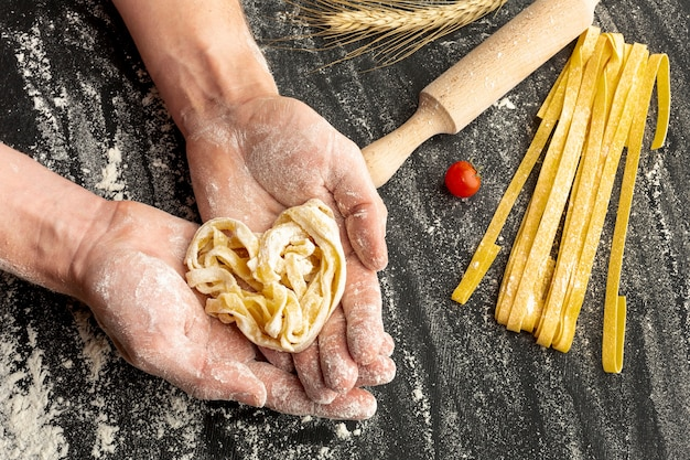 Chef holding uncooked pasta in hands Free Photo