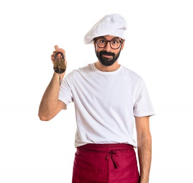 흰색 배경 위에 빈티지 자물쇠를 들고 요리사 무료 사진