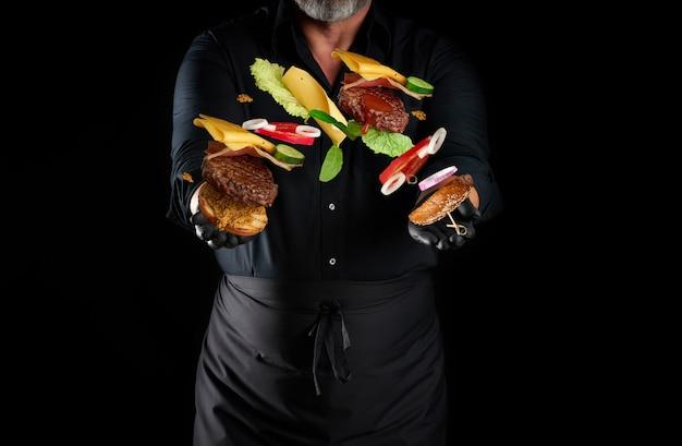 黒いシャツ、エプロン、ラテックスの黒い手袋を着たシェフが、チーズバーガーの材料を飛ばしている手の中の黒いスペースに立っています:ゴマ、カツ、トマト、レタス、オニオンリング、チーズのパン Premium写真