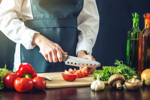 黒エプロンカット野菜のシェフ Premium写真