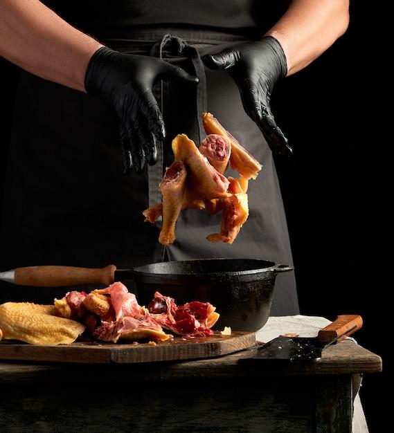 Шеф-повар в черной униформе и измельчающих латексных перчатках бросает нарезанную курицу в черную чугунную сковороду с деревянной ручкой Premium Фотографии