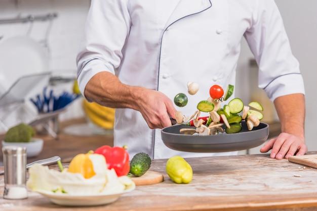 Шеф-повар на кухне приготовления пищи с овощами Premium Фотографии
