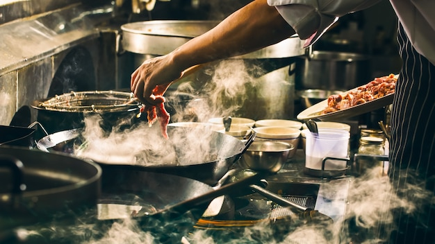 Chef is cooking beef in wok Premium Photo