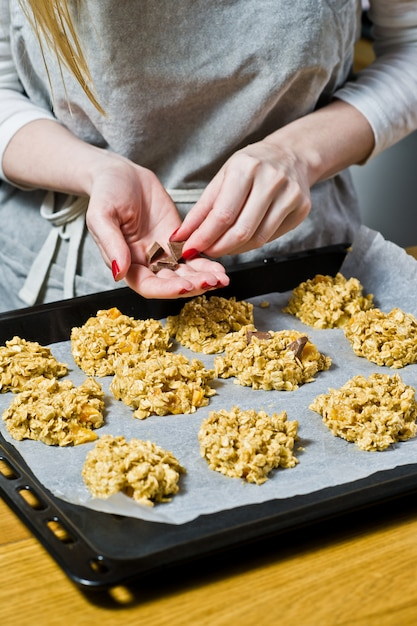 The chef is preparing cookies, spread the dough on the trays. Premium Photo
