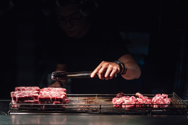 Chef is selecting a raw beef cube by tong for cooking with blow-torched in medium rare. Premium Photo