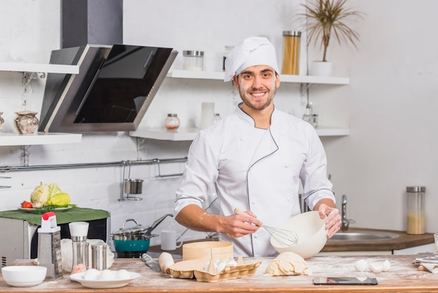 Chef in kitchen making dough Free Photo