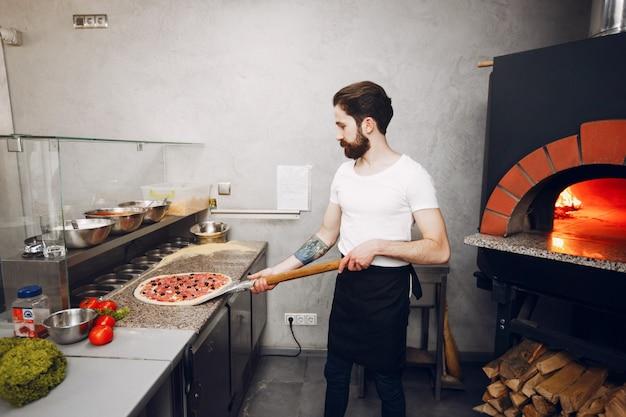 Chef in the kitchen prepares pizza Free Photo