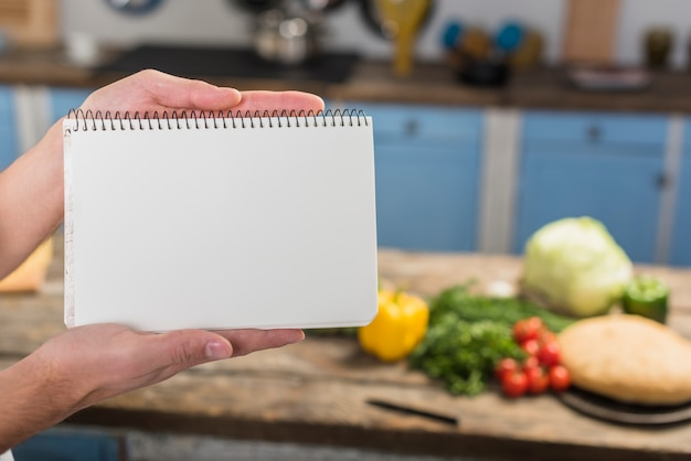 Chef in kitchen showing notepad Free Photo