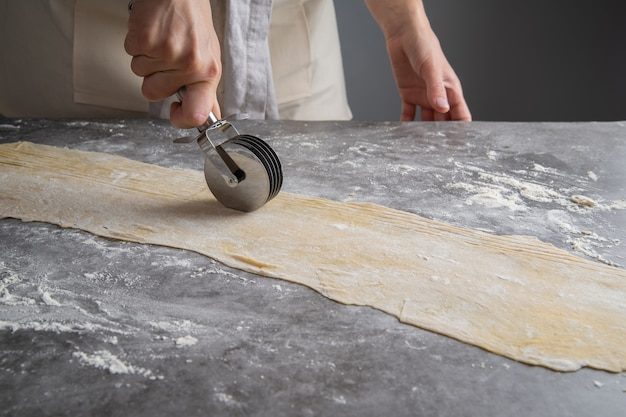 Chef making pasta out of dough Free Photo