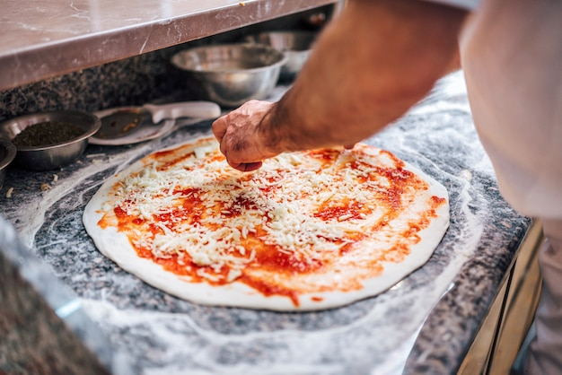 Chef making the pizza. close-up. adding cheese on pizza base. Premium Photo