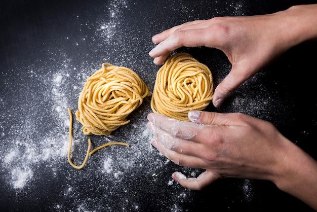 Chef making tagliatelle pasta nest with powder flour on kitchen table Free Photo