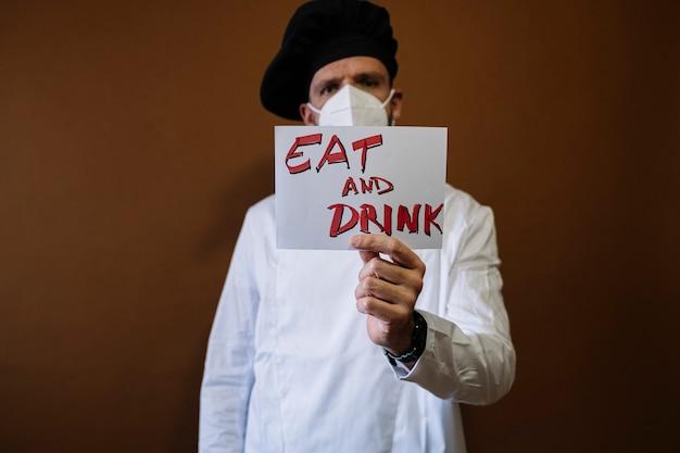 食べると飲むと書かれた看板を持っているシェフの男、彼は彼の顔にマスクを着用しています Premium写真