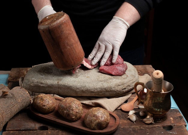 Chef mincing raw meat with wooden hammer on the stone Free Photo