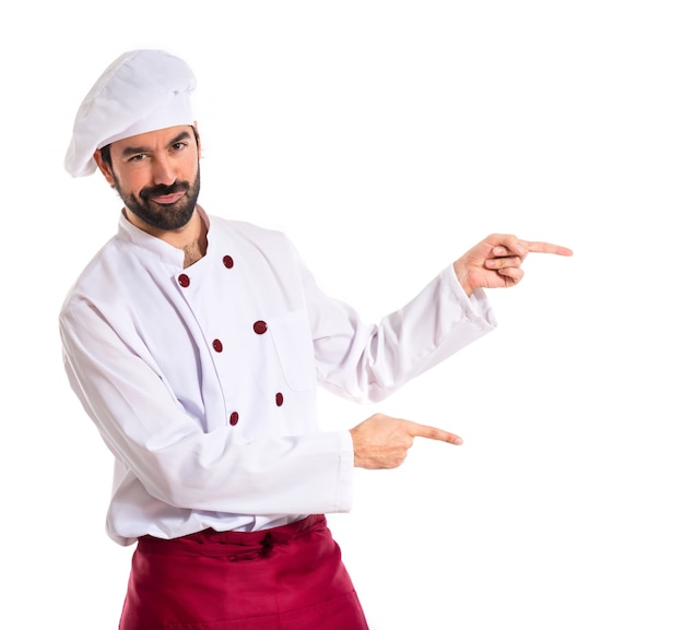 Chef pointing to the lateral over white background Free Photo